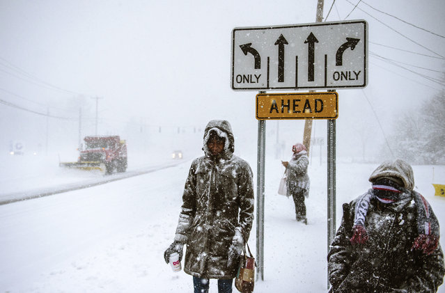 Charville Smith, left, Judy Simmons, center, and Cheryl Rosa stand at a Silver Lane bus stop, waiting for their ride home, after receiving a phone call from their employer, Cabela's, that it was closing due a snowstorm Thursday, February 9, 2017, in East Hartford, Conn. (Photo by Mark Mirko/Hartford Courant via AP Photo)
