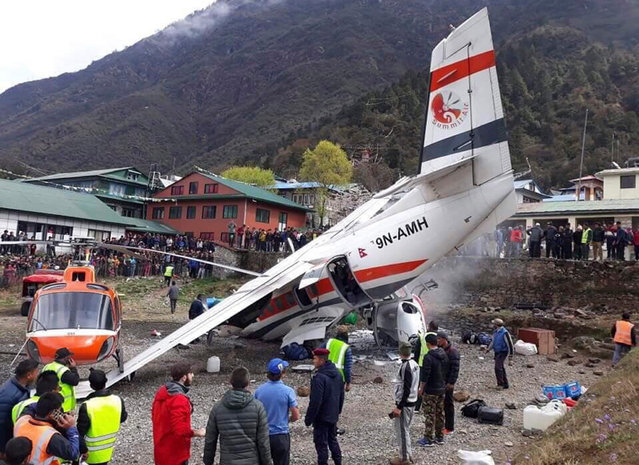 A view of the crash site of a domestic Summit Air aircraft and a helicopter at Lukla Airport, Solukhumbu district, Nepal, 14 April 2019. At least two people died and five were injured in the accident between a plane and a parked helicopter after take-off, according to media reports. (Photo by Ram Nepal/EPA/EFE)