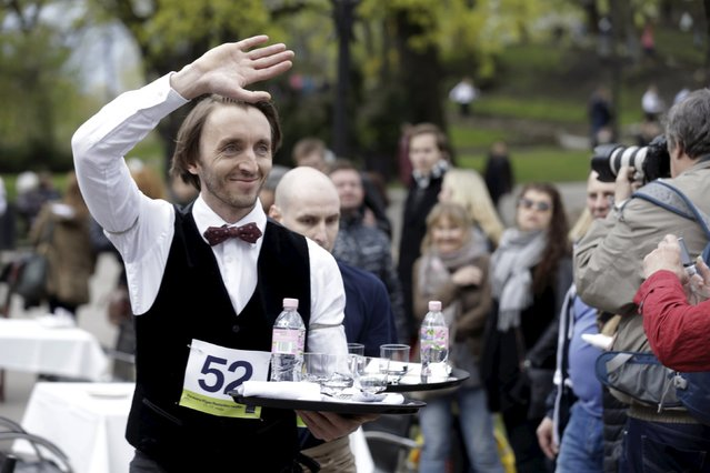 """A man waves to spectators as he competes in the """"Waiters Race"""" in Riga, Latvia May 2, 2015. (Photo by Ints Kalnins/Reuters)"""