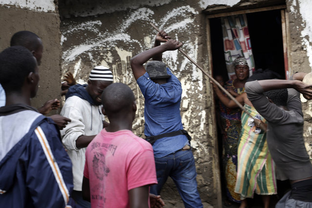 Demonstrators corner a suspected member of the ruling party's Imbonerakure youth militia at his home in the Cibitoke district of Bujumbura, Burundi, Thursday May 7, 2015. (Photo by Jerome Delay/AP Photo)