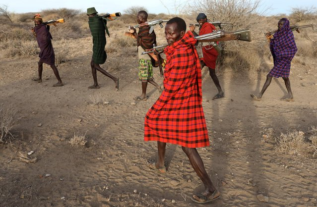 Turkana tribesmen walk with guns in order to protect their cattle from rival Pokot and Sambur tribesmen near Baragoy, Kenya February 14, 2017. Cattle rustling and competition for grazing have long troubled northern Kenya, but severe drought and political rivalries ahead of the elections have exacerbated the situation between ethnic tribes. (Photo by Goran Tomasevic/Reuters)