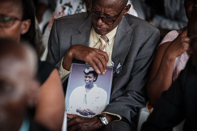 Vianney Rusanganwa, 61, holds a portrait of his late wife Liberatha Mukangira who died aged 31, during the mass funeral to bury 81 coffins containing newly discoverd remains of 84,437 victims of the 1994 genocide in the mass grave at the Nyanza Genocide Memorial, suburb of the capital Kigali, on May 4, 2019. The remains of nearly 85,000 people murdered in Rwanda's genocide were laid to rest on May 4 in a sombre ceremony in Kigali, a quarter of a century after the slaughter. (Photo by Yasuyoshi Chiba/AFP Photo)