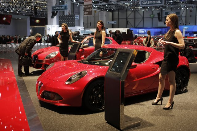 A man looks at a car as models pose in front of the new Alpha Romeo C4 during the media day of the 84th Geneva International Motor Show, Switzerland, Tuesday, March 4, 2014. (Photo by Laurent Cipriani/AP Photo)
