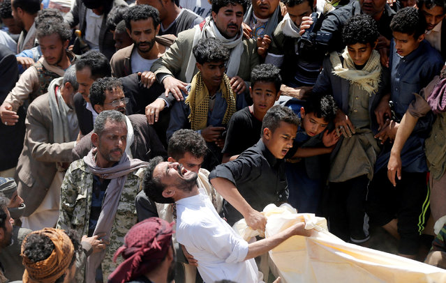 A man reacts as he lowers the body of his daughter to a grave during the burial of people who were killed by a blast in Sanaa, Yemen on April 10, 2019. (Photo by Khaled Abdullah/Reuters)