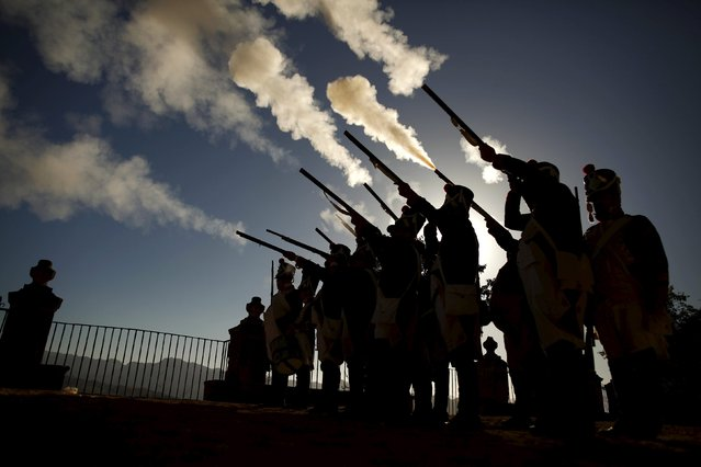 "Members of a historical battle re-enactment group dressed in early nineteenth century French army uniforms are silhouetted as they fire their weapons during the third edition of ""Ronda Romantica"" (Romantic Ronda) in Ronda, southern Spain, May 16, 2015. (Photo by Jon Nazca/Reuters)"