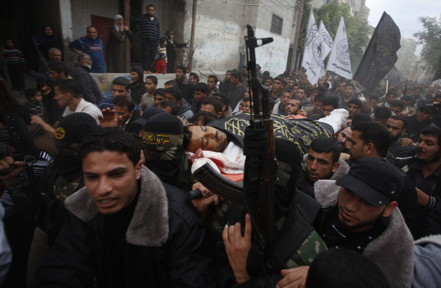 """Palestinians carry the body of an Islamic Jihad militant, who was killed in an Israeli air strike, during his funeral at a cemetery in Khan Younis in the southern Gaza Strip March 11, 2014. An Israeli air strike on Tuesday killed three Palestinian militants in the Gaza Strip, the Islamic Jihad group said. The Israeli military said an Israeli aircraft targeted Islamic Jihad members who had fired a mortar bomb at its forces, and """"direct hits were confirmed"""". (Photo by Ibraheem Abu Mustafa/Reuters)"""