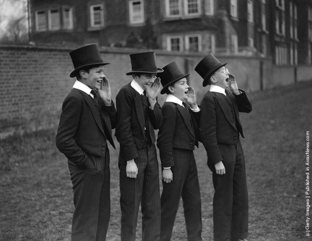 1928: A group of public school boys watch their classmates playing the Eton Wall Game, traditionally played between town and school on St Andrew's Day, and unique to Eton.