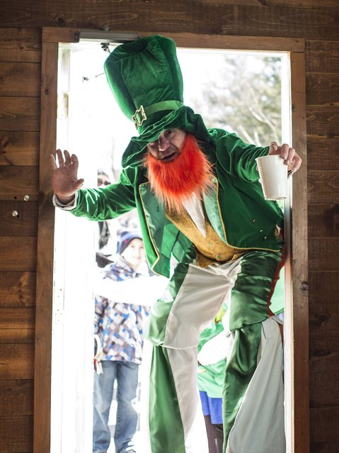 "A participant dressed as a leprechaun on stilts enters Keepers Pub at the finish of the ""World's Shortest"" Saint Patrick's Day Parade in West Boylston, Massachusetts. (Photo by C. J. Gunther/EPA)"