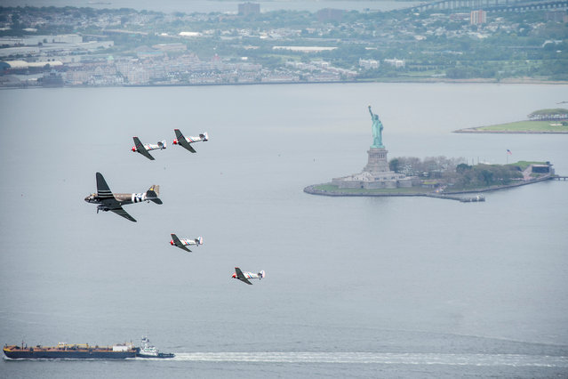 A squadron of vintage WWII airplanes used by the GEICO Skytypers accompanies a DC-3 through New York, ahead of the Bethpage Air Show as part of a Memorial Day event at Jones Beach on Long Island, New York, U.S., May 23, 2019. The DC-3 was the plane used to transport paratroopers into Normandy during WWII. (Photo by Johnny Milano/Reuters)