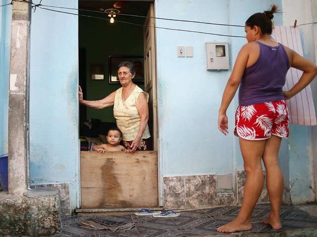 Josefa Soares de Olivera (Top C) stands with Vitor Soares near her home in favela. (Photo by Mario Tama/Getty Images)