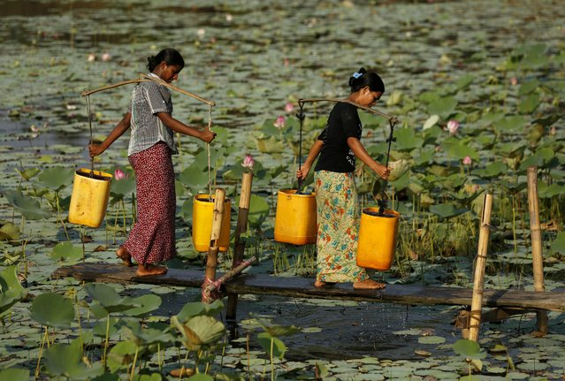 Women load pairs of water buckets as they collect fresh water at a pond of Dala township, the outskirt of Yangon, Myanmar, 20 April 2015. (Photo by Lynn Bo Bo/EPA)