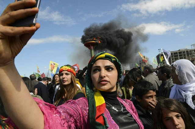 "A woman takes a selfie picture as Turkish Kurds gather as part of Newroz celebrations in Diyarbakir, on March 21, 2016. Nowruz, the Farsi-language word for ""New Year"", is an ancient Persian festival, celebrated on the first day of spring, on March 21, in Central Asian republics, Iraq, Turkey, Afghanistan and Iran. (Photo by Ilyas Akengin/AFP Photo)"