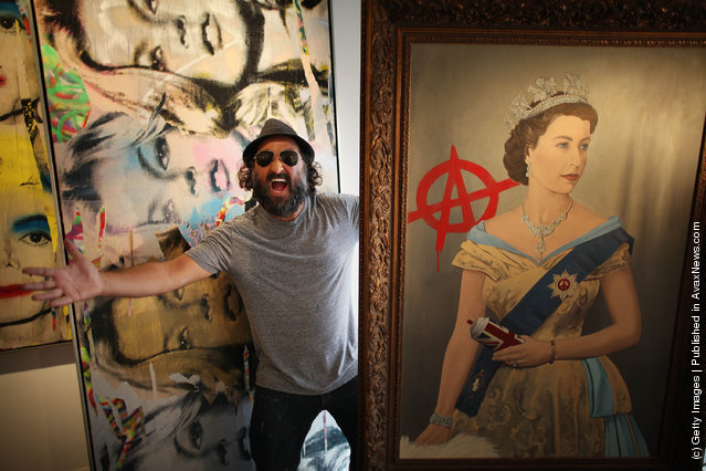Artist Mr Brainwash stands with his paintings 'The Queen' (R) and 'Kate Moss' at the Opera Gallery