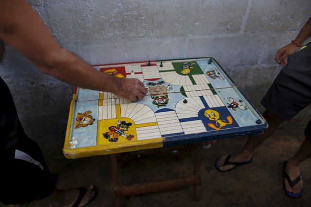 Inmates play a board game at the Pavilion No.6 assigned to foreigners at La Joya prison on the outskirts of Panama City, Panama January 29, 2016. (Photo by Carlos Jasso/Reuters)