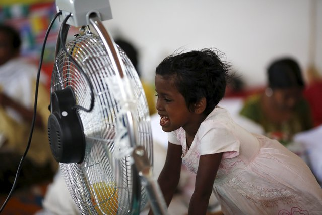 A young Rohingya migrant, who arrived recently by boat, stands in front of a fan at a temporary shelter in Kuala Langsa, in Indonesia's Aceh Province May 25, 2015. (Photo by Nyimas Laula/Reuters)