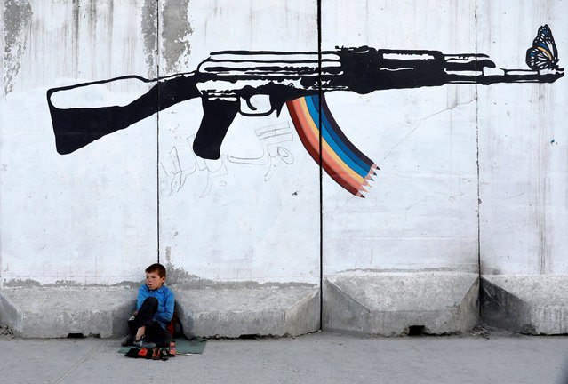 A shoe polisher waits for customers under graffiti on a wall in Kabul, Afghanistan on June 13, 2019. (Photo by Mohammad Ismail/Reuters)
