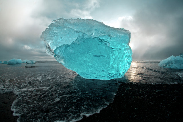 """""""Iceberg Gallery"""". Like a scene from a different time on earth, or a completely different planet altogether. Passed down through Jökulsárlón lagoon through an outlet of the Vatnajökull Glacier, Icebergs enter into the North Atlantic. Shaped and polished by the ocean, the tide leaves a magnificent gallery of huge iceberg sculptures on the volcanic black beaches of Iceland. Photographed here at sunset, just after a rain storm. (Photo and caption by Sam Morris/National Geographic Photo Contest)"""
