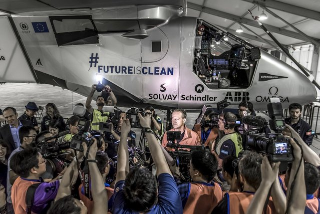 Photographers gather to take pictures of pilot Andre Borschberg (C) ahead of the take off of Solar Impulse 2-a solar powered plane- in Nanjing, China, May 31, 2015. The world's largest solar-powered airplane, Solar Impulse 2, took off from eastern China's Nanjing on Sunday to continue its round-the-world voyage. The Swiss-made plane left Nanjing's Lukou International Airport at 2:39 in the early morning, with former fighter pilot Borschberg at the controls alone for the entire 8,200-kilometer flight from Nanjing to Hawaii, the toughest leg of its marathon adventure.   REUTERS/Solar Impulse/Handout via Reuters
