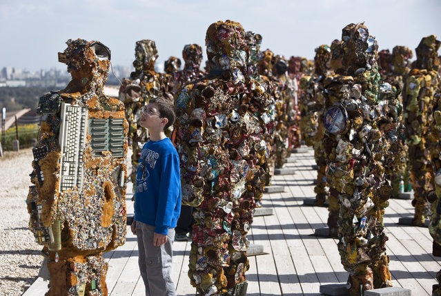 """A boy looks at a statue by German artist HA Schult during a preview of the artist's exhibition at the Ariel Sharon Park near Tel Aviv April 2, 2014. Schult's """"Trash People"""" exhibition, featuring 500 human-sized figures made from recycled materials, has been travelling worldwide for 18 years and opens this weekend near Tel Aviv. (Photo by Nir Elias/Reuters)"""