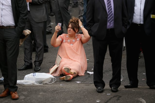 A racegoer uses the camera on her phone to check her hair on the opening day of the Grand National Festival at Aintree Racecourse on April 3, 2014 in Aintree, England. The three days of racing attracts thousands of racegoers and fans from across the world. The meeting culminates with millions of pounds being wagered on the runners taking part in Europe's richest jump race, the Grand National. (Photo by Christopher Furlong/Getty Images)