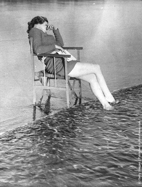 1938: The tide comes in on a woman at Barry Sands who has fallen asleep in the sunshine