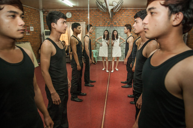 Sun Model assistant Miss Voleak teaches students how to pose for photos by looking at themselves in a mirror during training at the fashion school on March 31, 2014 in Phnom Penh, Cambodia. (Photo by Omar Havana/Getty Images)