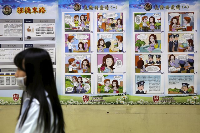 """People walk past cartoon posters entitled """"Dangerous Love"""" as part of a security campaign in Beijing, China, April 21, 2016. (Photo by Kim Kyung-Hoon/Reuters)"""