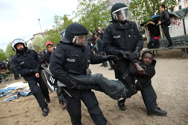 Police carry away a young protester after they intervened at the former temporary refugee camp at Oranienplatz in Berlin, Germany, on April 8, 2014. Several hundred riot police sealed off the square after, according to an eyewitness, violence broke out between refugees who had accepted a deal by the city to leave the camp and a small number who insisted on staying. Refugees, many of them from Africa who came to Germany via Lampedusa, began dismantling their shelters after agreeing to move to a renovated hostel.  (Photo by Sean Gallup/Getty Images)