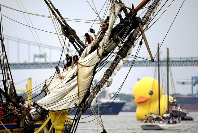 Crew members work on the L'Hermione as a giant rubber duck sails up the Delaware River between Camden, N.J. and Philadelphia during a tall ships parade, Thursday, June 25, 2015. A tall ship festival is scheduled to be open to the public through Sunday, June 28. Organizers say the event on both sides of the river will allow people a close-up view of famed ships such as the French vessel L'Hermione, Brazilian vessel Cisne Branco, Canadian Barque Picton Castle, and Philadelphia's own Gazela. (Photo by Matt Slocum/AP Photo)