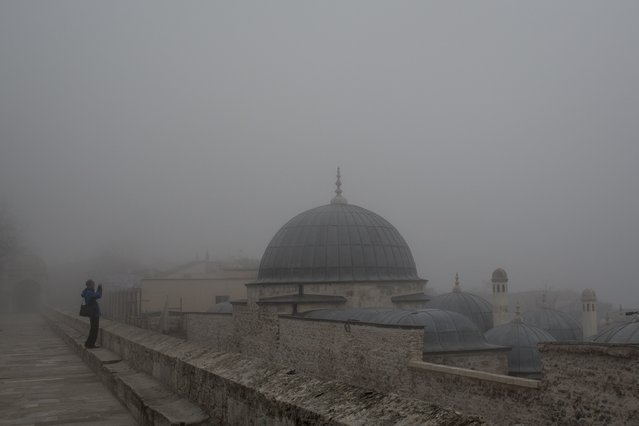A man tries to take a photograph of the Istanbul skyline under heavy fog from Suleymaniye Mosque on March 1, 2017 in Istanbul, Turkey. Fog covered Istanbul and the Bosphorus Strait for the second straight day keeping ferry services suspended. (Photo by Chris McGrath/Getty Images)