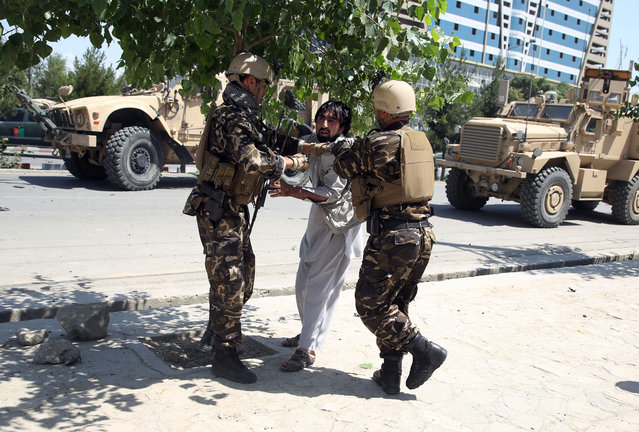 Afghan security forces beat a man at the site of a suicide car bomb attack on a NATO convoy in Kabul, Afghanistan, Tuesday, June 30, 2015. An eyewitness said the man was later released. (Photo by Massoud Hossaini/AP Photo)