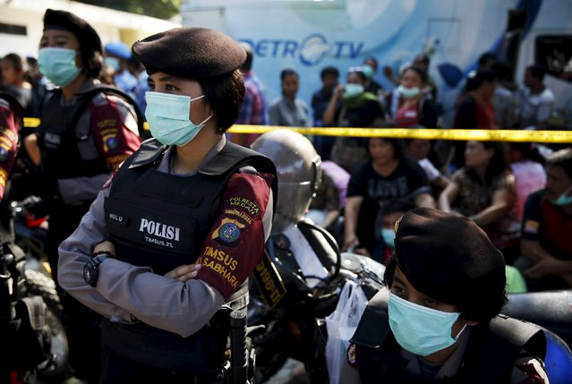 Indonesian police women stand guard near relatives of the victims of an Indonesian military C-130 Hercules transport plane that crashed into a residential area, outside the Adam Malik hospital in Medan, Indonesia North Sumatra province July 2, 2015. (Photo by Reuters/Beawiharta)