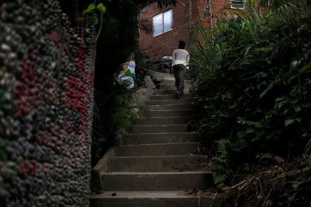 Solange, a worker at Pousada Favelinha hostel, returns to the hostel in Pereira da Silva favela, in Rio de Janeiro, Brazil, April 29, 2016. (Photo by Pilar Olivares/Reuters)