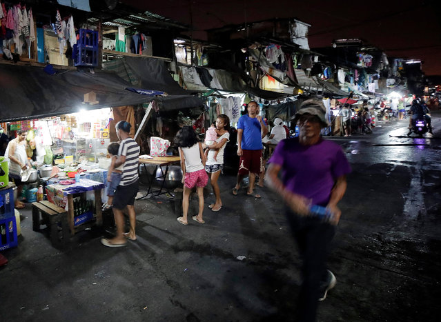 Filipino informal settlers are seen in front of shanties at a slum area in Manila, Philippines, 28 February 2019 (issued 13 June 2019). The metropolitan area of Manila has the largest slum area in the world, home to some four million people, a third of the inhabitants of the city, according to studies conducted by humanitarian organizations. (Photo by Francis R. Malasig/EPA/EFE)