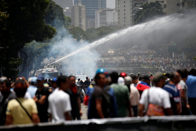 Police use a water cannon to disperse demonstrators during clashes with security forces during an opposition rally in Caracas, Venezuela on April 4, 2017. (Photo by Carlos Garcia Rawlins/Reuters)