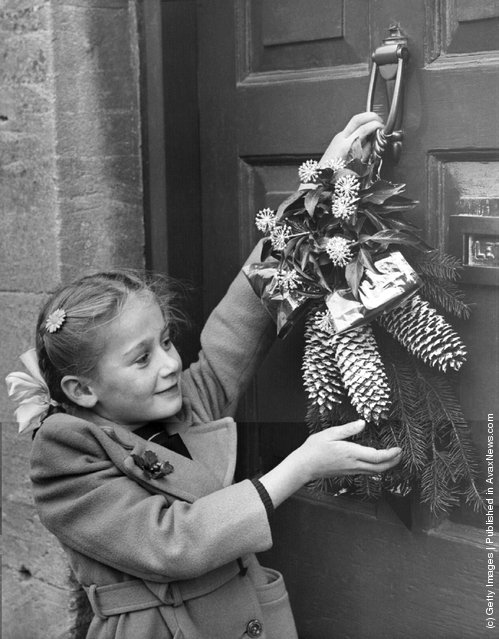 1954: A young girl hangs a Christmas garland on the door of her cottage home at Northleach, Gloucestershire, in accordance with an old local custom
