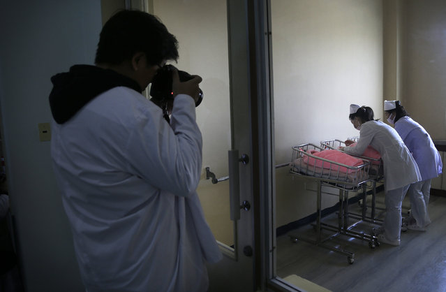 A foreign journalist photographs nurses tending to newborn babies at Pyongyang Maternity Hospital during a press tour on Saturday, May 7, 2016 in Pyongyang, North Korea. (Photo by Wong Maye-E/AP Photo)