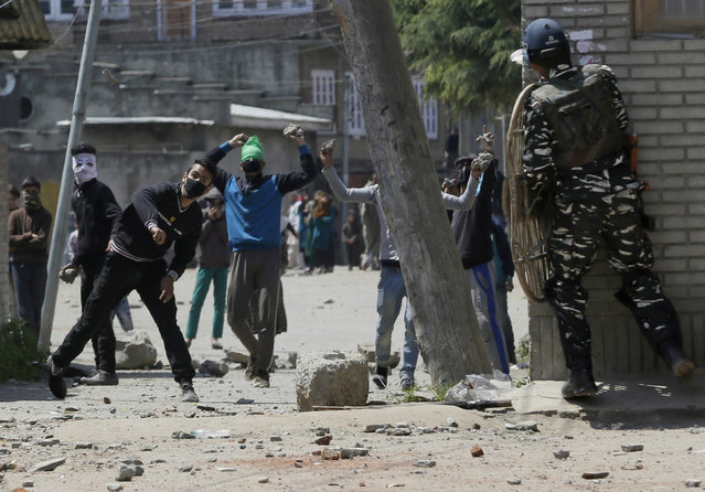 Kashmiri protesters throw stones on Indian security men outside a poling station during a by-election to an Indian Parliament seat in Srinagar, Indian controlled Kashmir, Sunday, April. 9, 2017. (Photo by Mukhtar Khan/AP Photo)