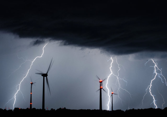 A long exposure of lightning flashing behind wind turbines near Wardenburg, Germany, during a morning thunderstorm early on July 3, 2015. (Photo by Sven Koopmann/EPA/Photoka)