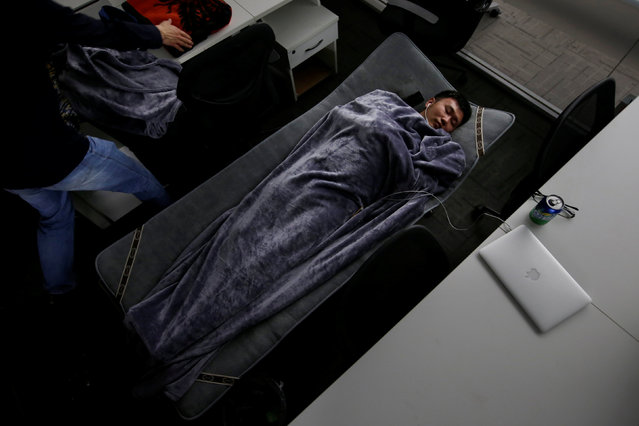 Han Liqun (C), a HR manager of RenRen Credit Management Co., sleeps on a camp bed at the office after finishing work early morning, in Beijing, China, April 27, 2016. (Photo by Jason Lee/Reuters)