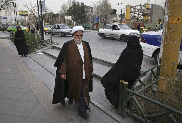 A clergyman make his way in a sidewalk in downtown Tehran, Iran, Sunday, February 28, 2016. (Photo by Vahid Salemi/AP Photo)