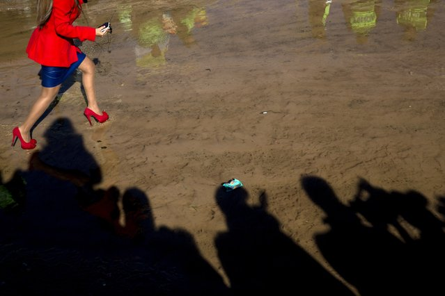 A TV reporter walks through the mud toward people waiting for Pope Francis to arrive to Palmasola prison in Santa Cruz, Bolivia, Friday, July 10, 2015. Palmasola is the most notorious of Bolivia's 32 prisons, built to detain some 800 people but housing 5,000, more than four in five still awaiting trial. Inmates have the run of the place, drugs are cheaper than on the street and money buys survival. (Photo by Rodrigo Abd/AP Photo)