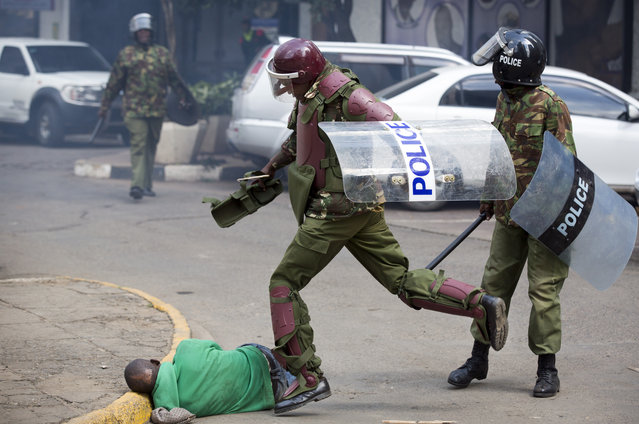 A Kenyan riot policeman repeatedly kicks a protester as he lies in the street after tripping over while trying to flee from them, during a protest in downtown Nairobi, Kenya, Monday, May 16, 2016. (Photo by Ben Curtis/AP Photo)