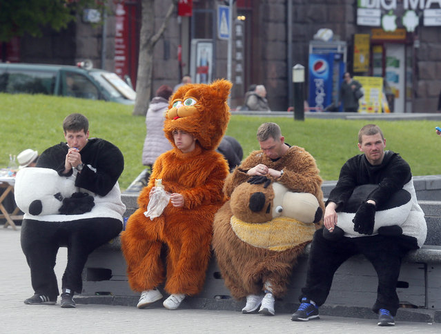 People dressed as cartoon characters to promote the Eurovision Song Contest, take a break in Kiev, Ukraine, Friday, April 28, 2017. Kiev will host the Eurovision Song Contest with the final taking place on Saturday May 13. (Photo by Efrem Lukatsky/AP Photo)