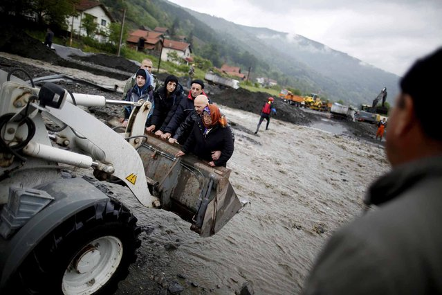 People are carried by a front loader as they evacuate from their flooded houses in Topcic Polje, near Zepce May 16, 2014. The heaviest rains and floods in 120 years have hit Bosnia and Serbia, killing five people, forcing hundreds out of their homes and cutting off entire towns. (Photo by Dado Ruvic/Reuters)