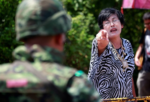 A pro-government protester points at a soldier during a cleanup at a pro-government demonstration site on the outskirts of Bangkok, Thailand Friday, May 23, 2014. Thailand's ruling military on Friday summoned the entire ousted government and members of the politically influential family at the heart of the country's long-running conflict, a day after it seized control of this volatile Southeast Asian nation in a non-violent coup. (Photo by Wason Wanichakorn/AP Photo)