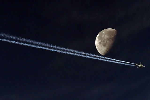 A jetliner leave a vapour trail as it passes in front of the moon on May 20, 2014, taken from the Algerian capital Algiers. (Photo by Farouk Batiche/AFP Photo)