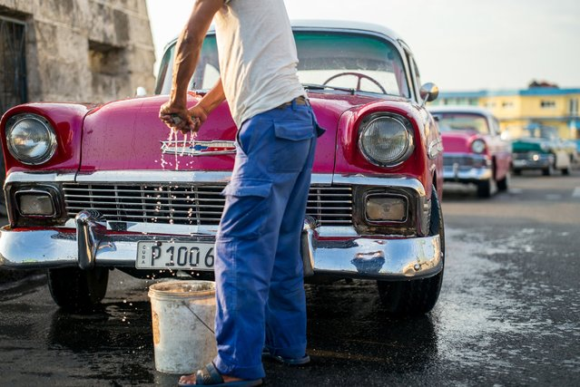 A man washes a series of 1950s Chevy taxis parked in the old port of Old Havana in the early morning of May 2, 2016. A few hours later, the first American cruise ship in decades entered the port. (Photo by Dotan Saguy)