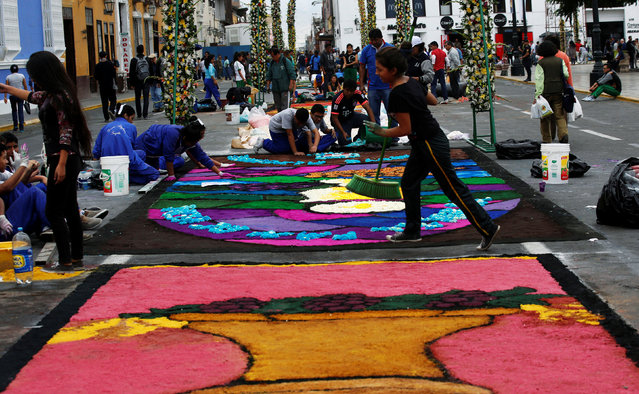 People prepare a sawdust and flower carpet during the feast of Corpus Christi in downtown Trujillo, Peru, May 26, 2016. (Photo by Mariana Bazo/Reuters)