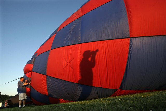 A photographer's shadow is cast on a hot air balloon as it is inflated by a crew during the 33rd annual QuickChek New Jersey Festival of Ballooning at Solberg Airport Friday, July 24, 2015, in Readington, N.J. (Photo by Mel Evans/AP Photo)